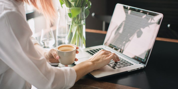 A woman drinking coffee and using a laptop